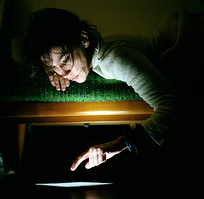 Woman typing on a computer at night - p1610m2181501 by myriam tirler