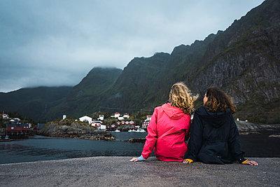 Norway, Lofoten, rear view of two young women sitting on a pier at the coast - p300m2042245 by Kike Arnaiz