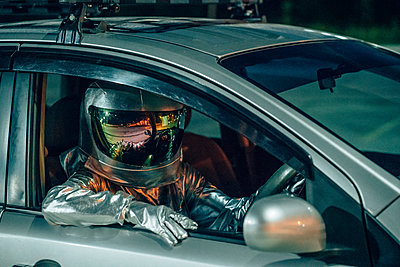 Spaceman sitting in car at night - p300m2043156 by Vasily Pindyurin