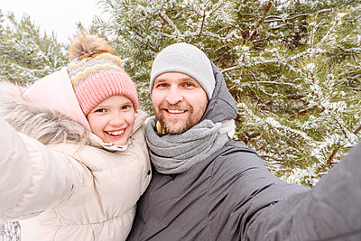 Smiling father and daughter against trees in forest during winter - p300m2251645 by Ekaterina Yakunina