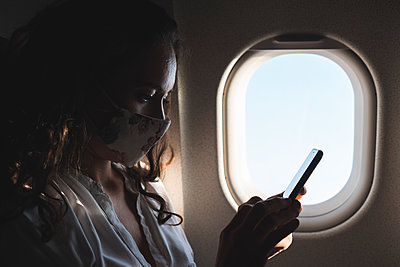 Female professional using smart phone in airplane during pandemic - p300m2293532 by Josu Acosta