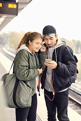 Young couple listening music through mobile phone on subway platform - p426m1003751f by Maskot