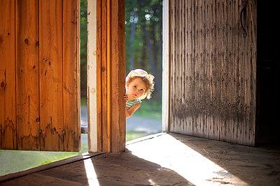 Curious girl peering around open door - p555m1409488 by Shestock