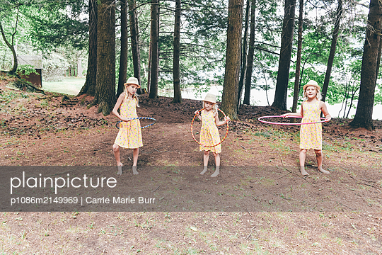 Three girls playing with Hula hoop - p1086m2149969 by Carrie Marie Burr