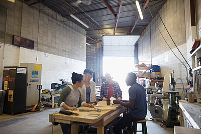 Design professional engineers brainstorming at workbench in workshop - p1192m1202059 by Hero Images