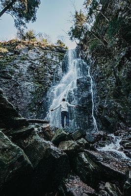 Man is standing in front of a waterfall - p1455m2092377 von Ingmar Wein