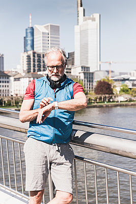 Athletic mature man with headphones taking the time on bridge in the city - p300m1588089 von Uwe Umstätter