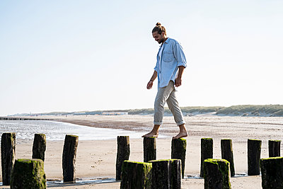 Smiling young man walking on wooden posts at beach against clear sky - p300m2227224 by Uwe Umstätter