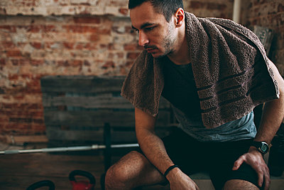 Thoughtful sporty man sitting in gym - p301m1130866f by Vasily Pindyurin