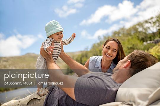 Familie mit Baby entspannt sich am Seeufer - p1355m1574051 von Tomasrodriguez