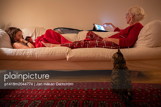 Katze beobachtet Oma und Enkeltochter auf dem Sofa - p1418m2044774 von Jan Håkan Dahlström