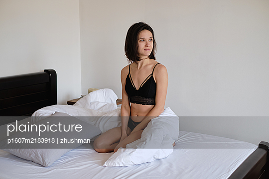 Young brunette woman sitting in her bed at morning - p1607m2183918 by zhushman