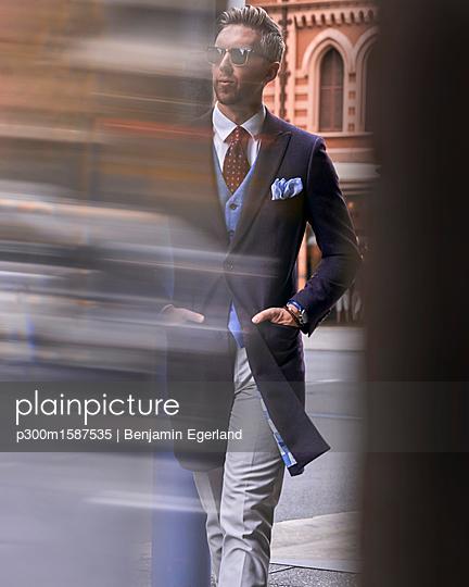 Fashion blogger Steve Tilbrook walking in the city - p300m1587535 von Benjamin Egerland