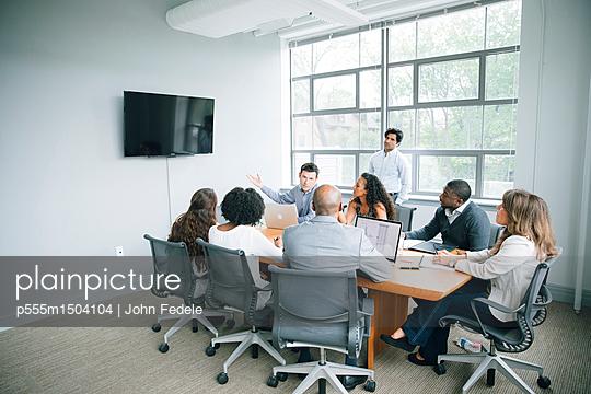 Businessman talking near visual screen in meeting - p555m1504104 by John Fedele