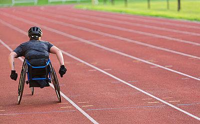 Female paraplegic athlete speeding along sports track in wheelchair race - p1023m2067590 by Martin Barraud