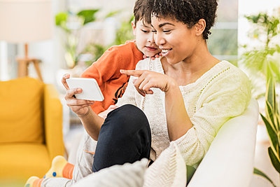 Smiling mother showing mobile phone to son while sitting at home - p300m2244130 by Uwe Umstätter