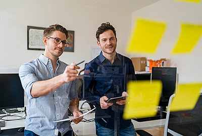 Smiling male colleagues discussing over adhesive notes at office - p300m2265318 by Daniel Ingold