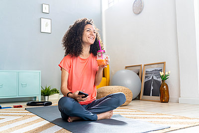 Cheerful woman having juice sitting with mobile phone on mat in living room - p300m2275440 by Giorgio Fochesato
