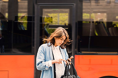 Young woman using mobile phone against bus - p426m1108204f by Maskot