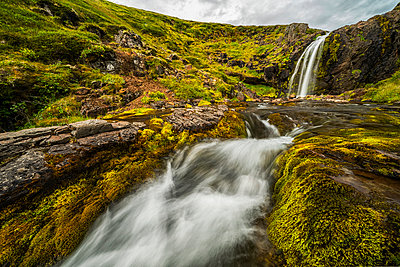 Water falling from rocky cliff to a stream below; Iceland - p442m2074058 by Robert Postma