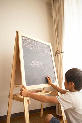 Boy drawing on blackboard - p5143213f by Doable
