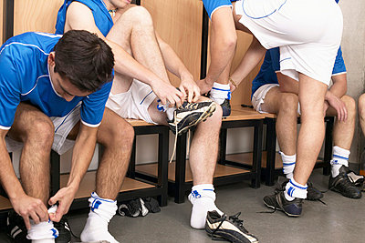 Footballers putting on boots - p92410342f by Image Source