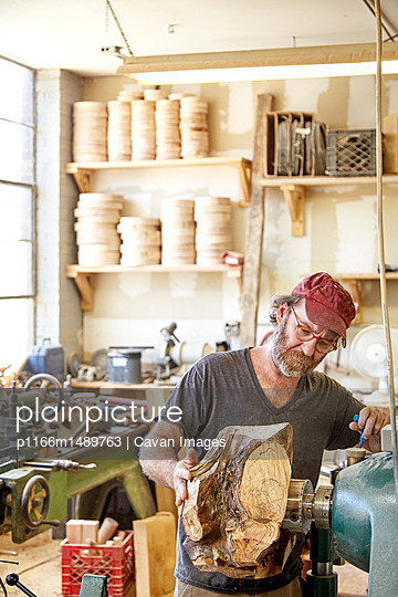 Carpenter using machinery in workshop - p1166m1489763 by Cavan Images