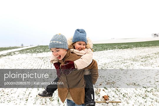 Boy carrying happy sister piggyback in winter landscape - p300m2080970 von Katharina Mikhrin