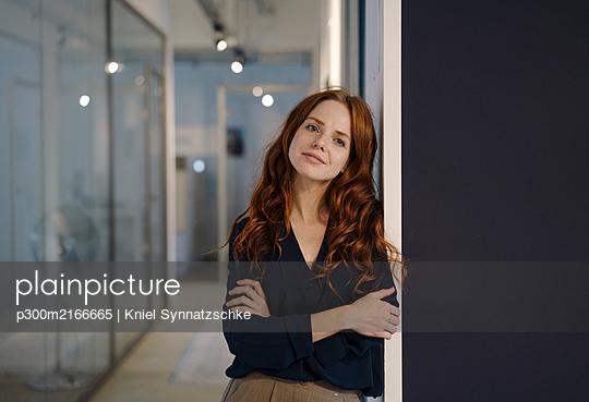 Portrait of smiling redheaded woman on office floor - p300m2166665 von Kniel Synnatzschke