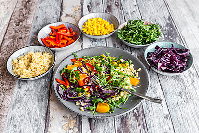 Plate of rainbow salad with bulgur, rocket and different vegetables and bowls with ingredients - p300m1356436 by Sandra Roesch