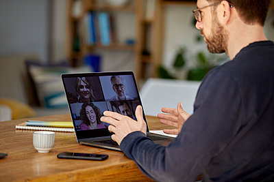 Mature businessman discussing with colleagues on video call through laptop over table - p300m2277406 by Büro Watzmann