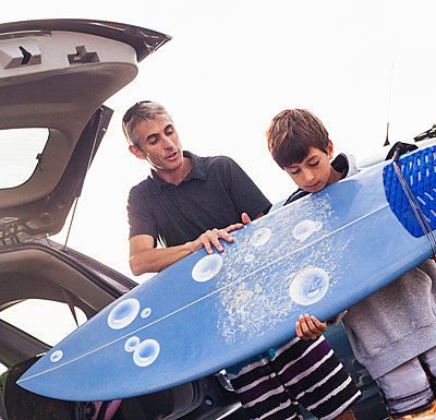 Father and son checking surfboard - p429m884146 by Yew! Images