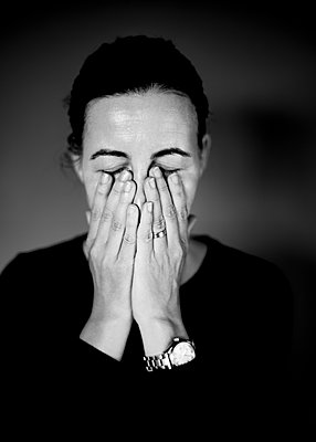 Dark-haired woman covers face with her hands - p552m2289373 by Leander Hopf