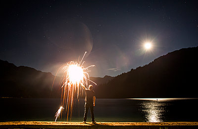 Caucasian man holding sparkler on waterfront at night - p555m1303587 by Adam Hester