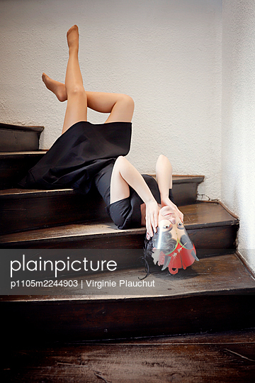 Woman with black dress lying on staircase - p1105m2244903 by Virginie Plauchut