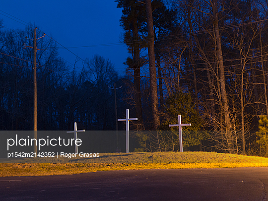 Three white crosses on a mound at night - p1542m2142352 by Roger Grasas