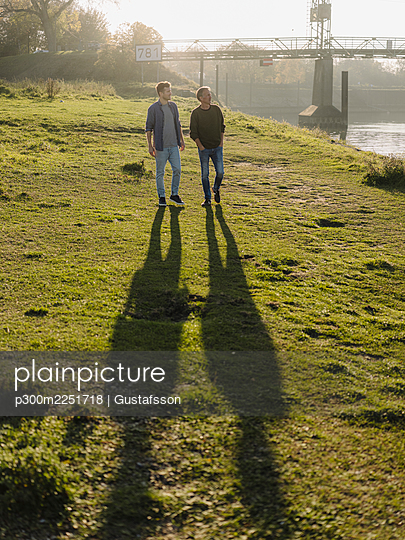 Son and father walking together on grass during autumn - p300m2251718 by Gustafsson