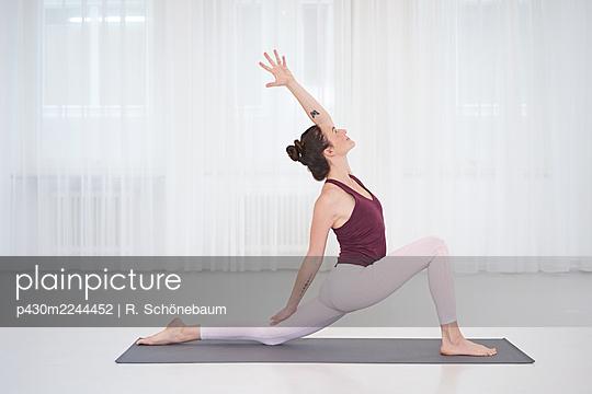 Woman practicing yoga in gym - p430m2244452 by R. Schönebaum