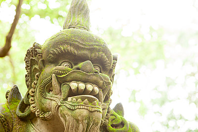 Stone carved demon Balinese statue with trees in the background, UBUD - p1166m2093900 by Cavan Images