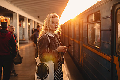 Young woman with smart phone standing at subway station - p1166m2153528 by Cavan Images
