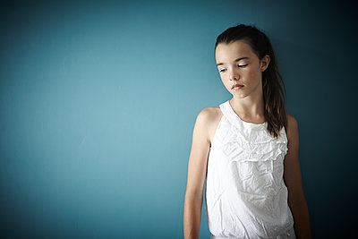 GIRL LEANING ON A BLUE WALL - p1430m1503578 by Charlotte Bresson