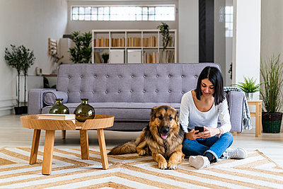 Woman using mobile phone while sitting on carpet with dog in living room - p300m2266100 by Giorgio Fochesato
