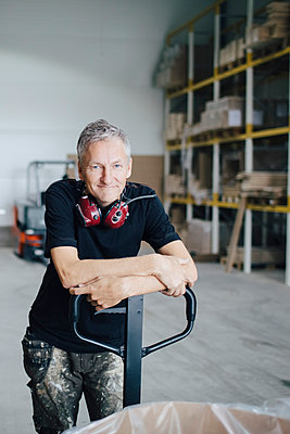 Portrait of mature worker leaning on pallet jack by stack at industry - p426m1537054 by Maskot