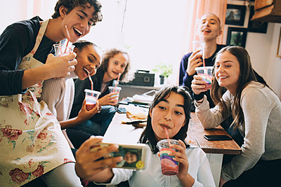 Teenage girl taking selfie with friends through mobile phone while enjoying smoothie at home - p426m2145501 by Maskot
