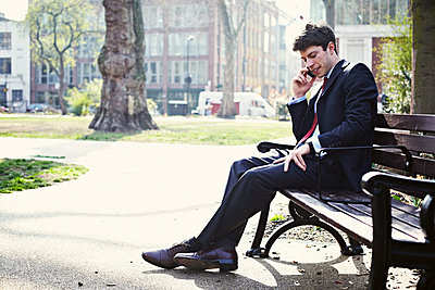 Businessman on park bench on cell phone - p429m803579f by Liam Norris