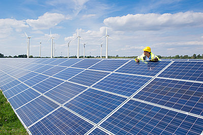 Mixed race man checking solar panels - p555m1478972 by Dave and Les Jacobs