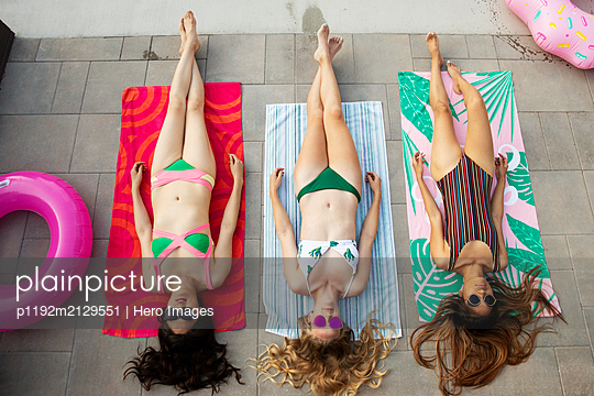 View from above beautiful young women friends relaxing, sunbathing on summer patio - p1192m2129551 by Hero Images