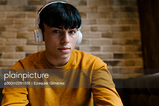 Young man wearing headphones staring while sitting at cafe - p300m2251035 by Ezequiel Giménez