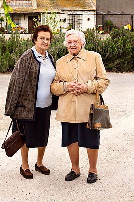 Portrait of senior females standing on road in city - p1166m979797f by Cavan Images