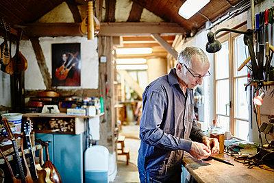 Gitarrenbauer arbeitet in seiner Werkstatt - p1359m1221837 von Great Images